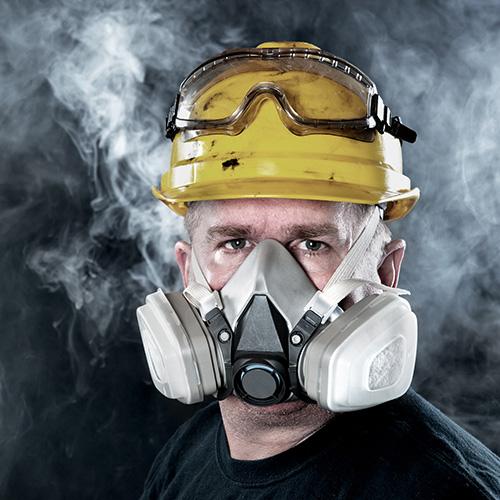 Mann mit Atemschutzmaske und Schutzhelm