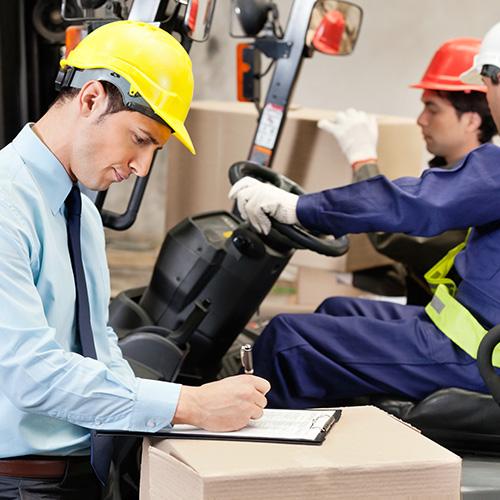 Mann mit Schutzhelm notiert etwas auf einem Klemmbrett