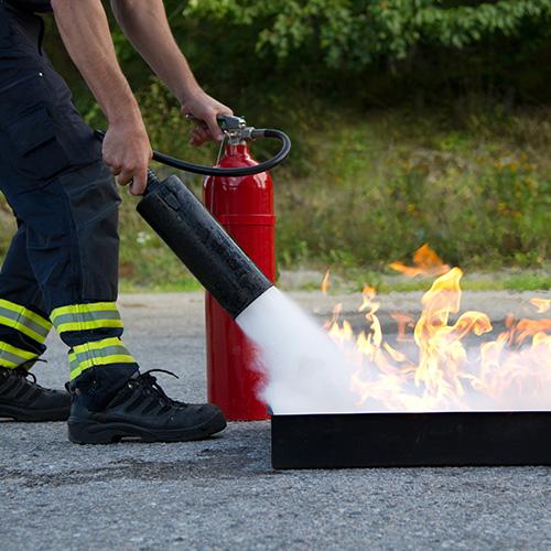 Mann mit Feuerlöscher löscht einen Brand