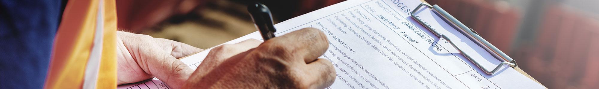 Arbeiter notiert etwas auf einem Blatt