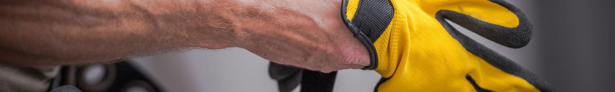 Mann zieht gelbe Sicherheitshandschuhe an
