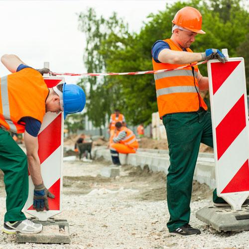Zwei Straßenarbeiter stellen Fahrbahnbegrenzungen auf