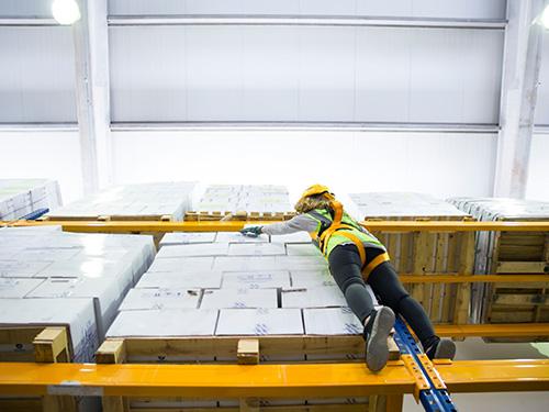 Junge Lagermitarbeiterin Arbeitssicherheit
